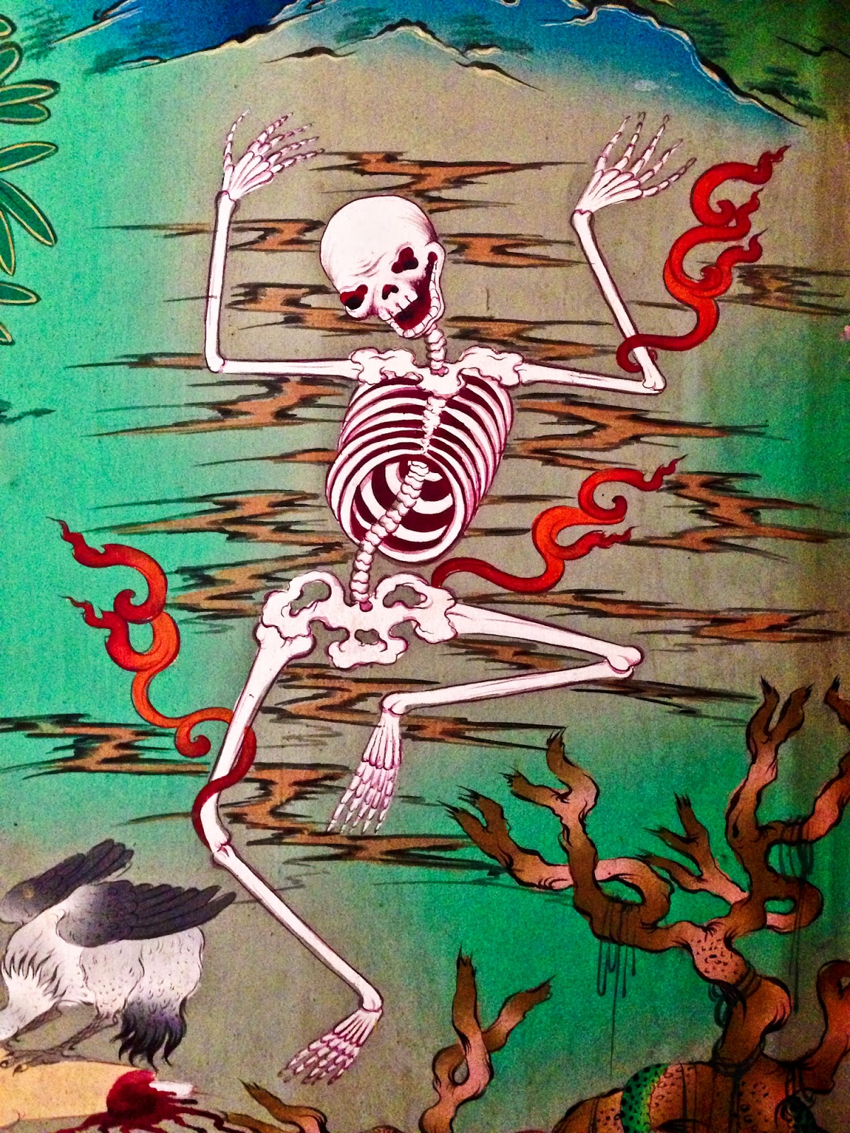 Tibetan Buddhist skeleton dancing in reds and greens.